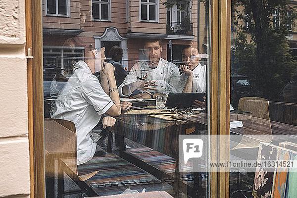 Männliche und weibliche Köche diskutieren am Restauranttisch durch ein Glasfenster gesehen