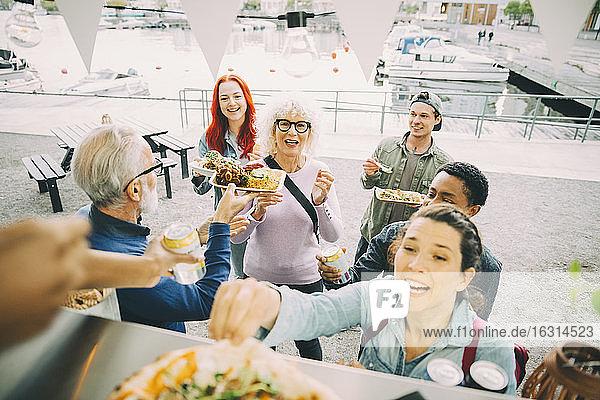 Lächelnde männliche und weibliche Kunden  die sich am Speisewagen in der Stadt vergnügen