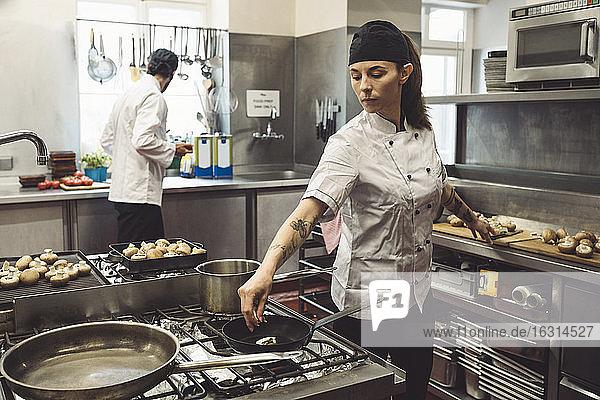 Männliche und weibliche Köche bei der Zubereitung von Speisen in der Großküche
