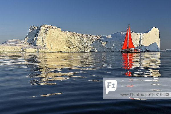 Red sailing boat in front of icebergs  Icefjord  UNESCO World Heritage  Disko Bay  Ilulissat  West Greenland  Greenland  North America