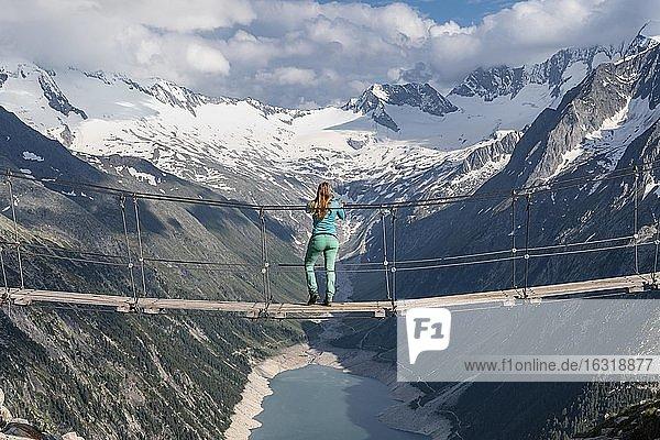 Wanderin  Frau auf Hängebrücke an der Olpererhütte  Schlegeisstausee  Speicher Schlegeis  Zillertaler Alpen  Gletscher Schlegeiskees  Zillertal  Tirol  Österreich  Europa
