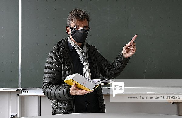 Teacher with thick winter jacket  scarf and face mask in classroom teaching  Corona crisis  Stuttgart  Baden-Württemberg  Germany  Europe