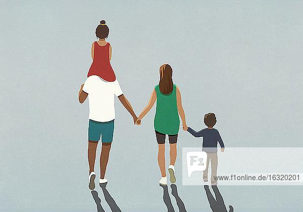 Zärtliche Familie  die sich an den Händen hält und spazieren geht