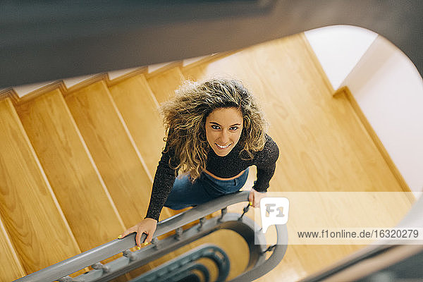 Portrait smiling young woman on wooden staircase