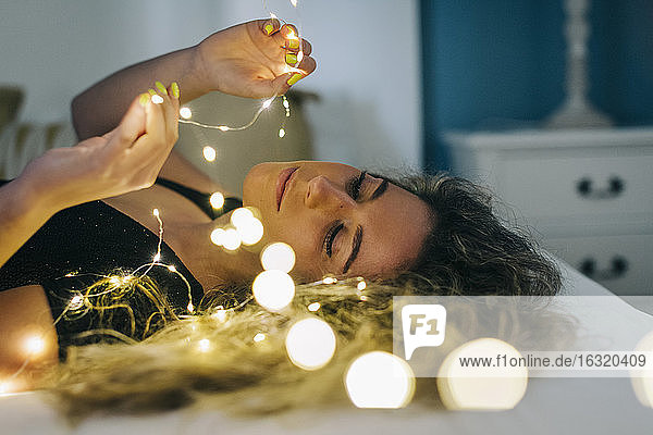 Young woman holding string lights on bed