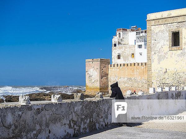 Morocco  Essaouira  Berber in black djellaba at harbor wall