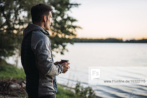 Man looking at the lake  drinking coffee