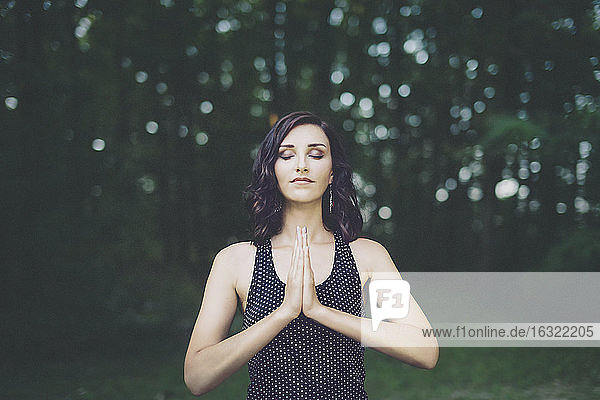 Young woman meditating with closed eyes in the forest  yoga in nature