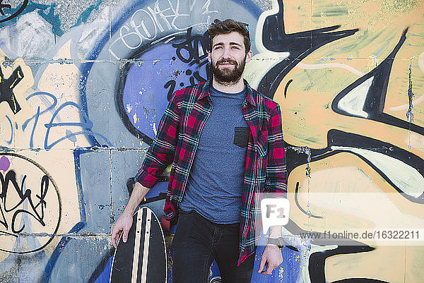 Spain  La Coruna  portrait of hipster leaning against wall with his longboard