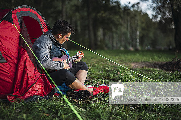 Man camping in Estonia  sitting in his tent  playing the ukulele