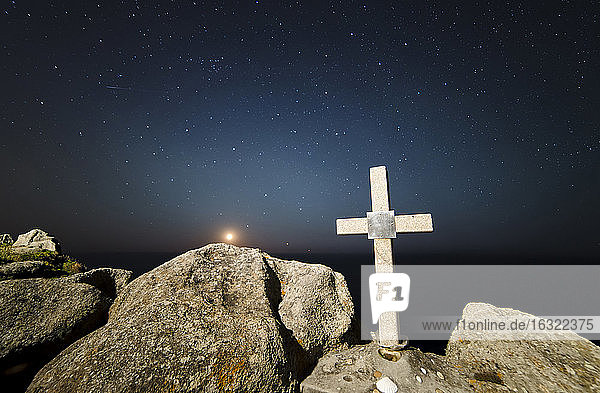 Spain  Galicia  Ferrol  Moonset in a place of the galician coast with a stone cross on the foreground