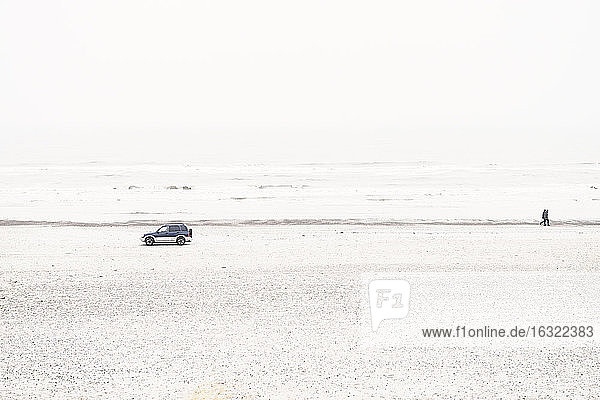 Denmark  Henne Strand  Car and walking couple at the beach
