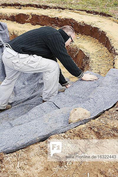 Mann beim Verlegen einer Filzunterlage für den Teich Mann beim Verlegen einer Filzunterlage für den Teich