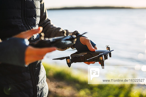 Man holding drone and telecontrol at a lake