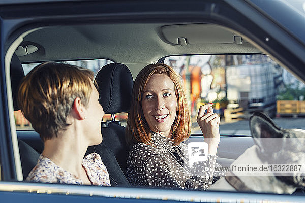 Two female friends sitting in their car talking together