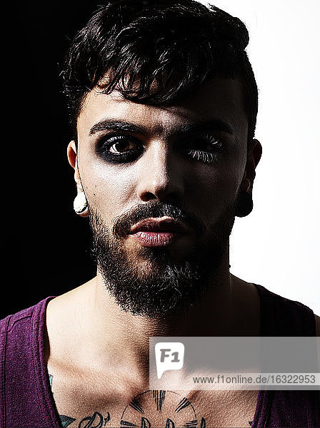 Portrait of man with full beard and earing wearing eye make up
