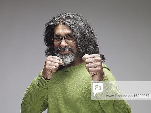 Mature man showing fists  looking confident  portrait