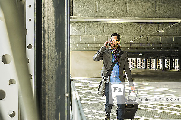 Young businessman walking in car park talking on cell phone
