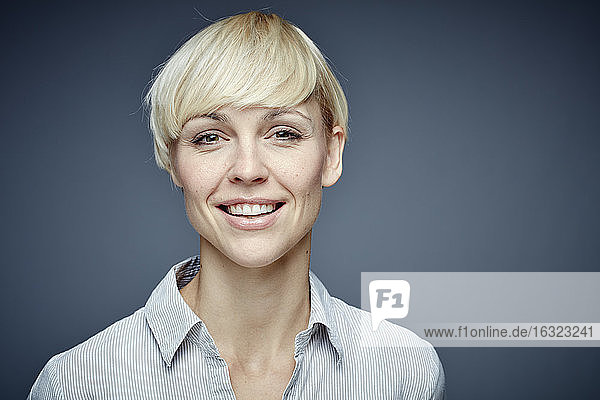 Portrait of smiling blond woman in front of grey background