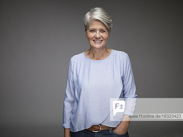 Portrait of mature woman with grey hair in front of grey background