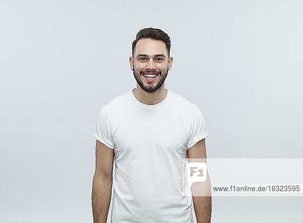 Portrait of laughing young man in front of light background