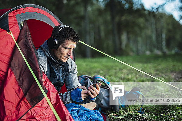 Man camping in Estonia  sitting in his tent  lietsning music from his smartphone