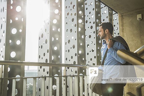 Young businessman with digital tablet looking out of window