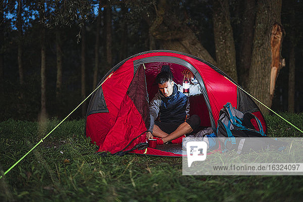 Man camping in Estonia  sitting in his tent  holding latern