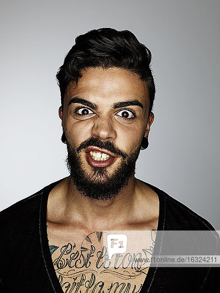 Portrait of angry man with tatoo on his chest