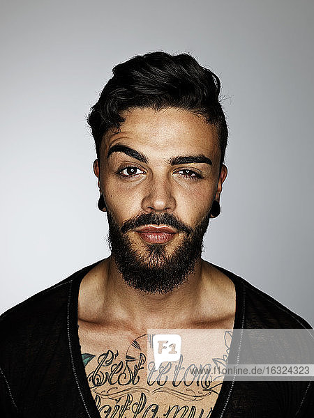 Portrait of man with tatoo on his chest raising eyebrow