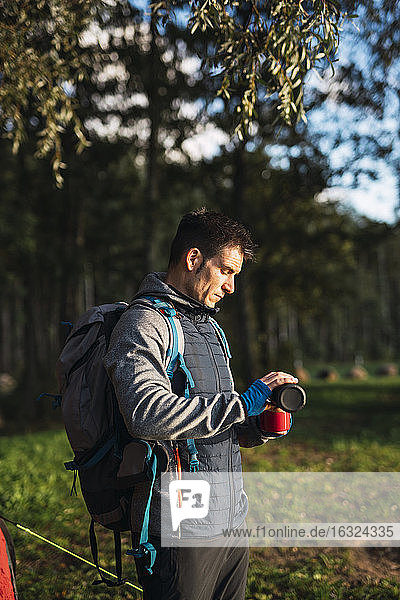 Man camping in Estonia  pouring water in a cup