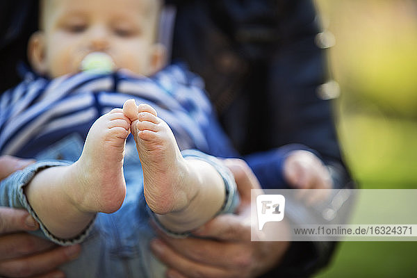 Feet of baby boy holding by his father