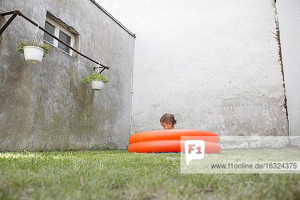 Deutschland  Freiburg  kleines Mädchen sitzt im Planschbecken im Hinterhof