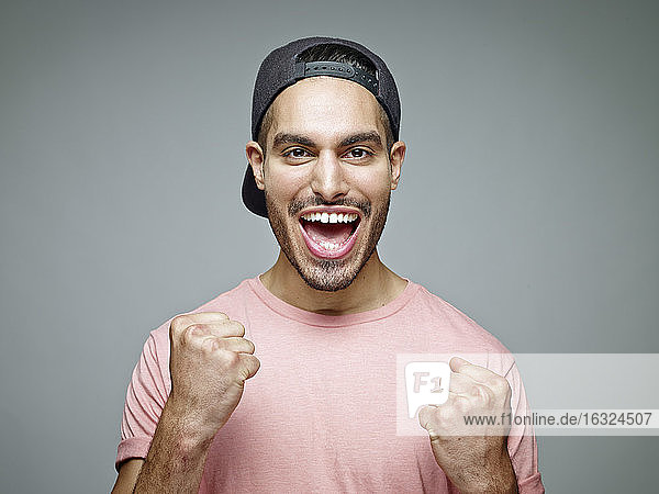 Portrait of man with baseball cap screaming for joy in front of grey background