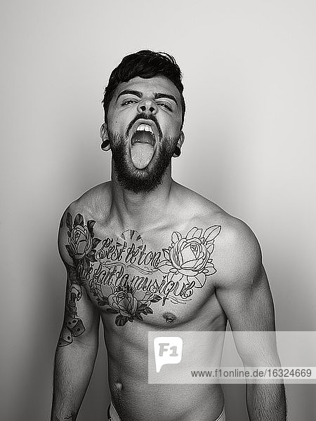 Portrait of man with tatoo on his chest sticking out tongue