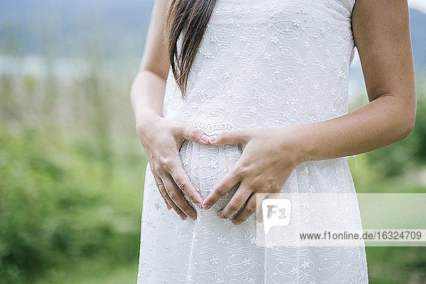 Frau macht herzförmigen Fingerrahmen auf dem Bauch