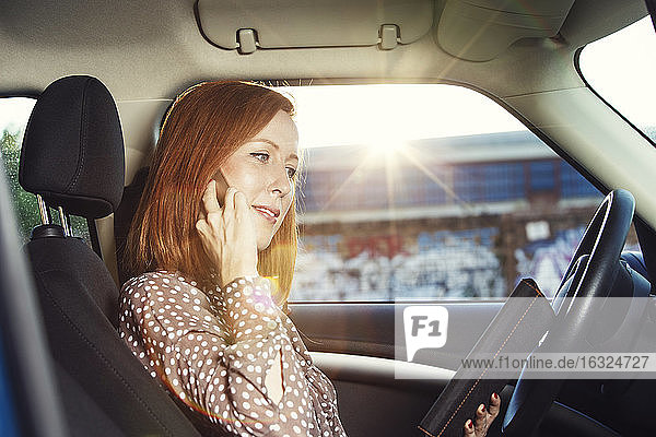 Redheaded businesswoman sitting in her car telephoning with smartphone