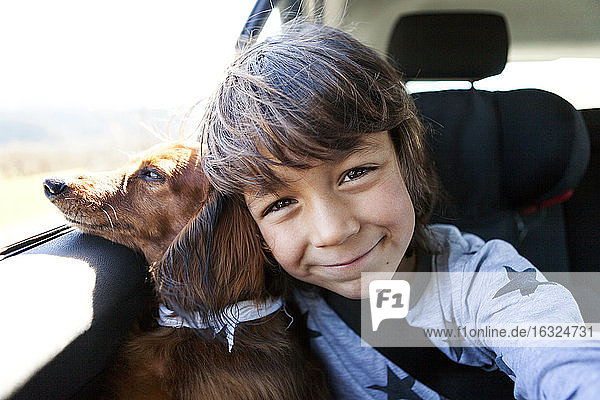 Portrait of smiling little boy sitting with his long-haired dachshund in a car