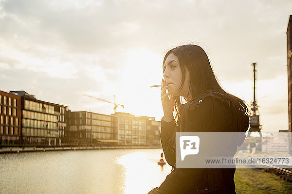 Germany  Muenster  young woman smoking cigarette in front of city harbour