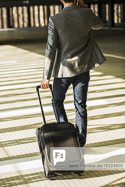 Young businessman with baggage walking in car park