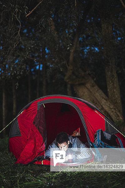 Man camping in Estonia  drawing in his sketchbook at night