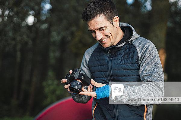 Man camping in Estonia  looking at his camera