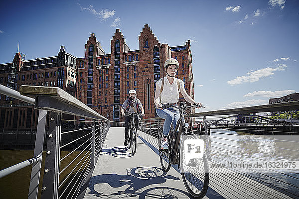 Germany  Hamburg  couple riding electric bicycles on bridge at Old Warehouse District