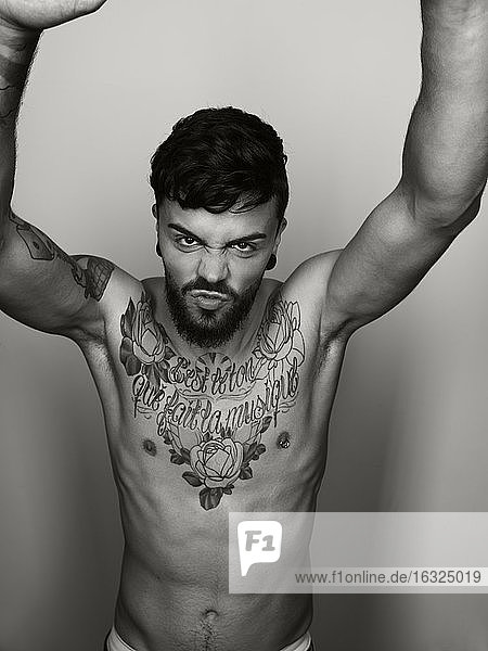 Portrait of angry man with tatoo on his chest stretching out his arms