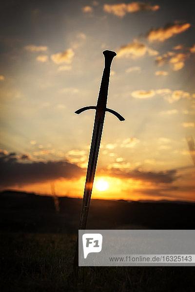 Sword in rural landscape at sunrise