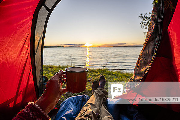 Man camping in Estonia  watching sunset lying in tent