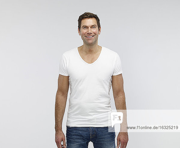Portrait of smiling mature man in front of white background