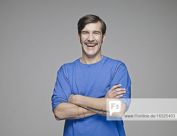 Portrait of laughing man with crossed arms in front of grey background
