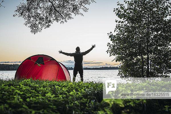 Man camping in Estonia  stretching at lake