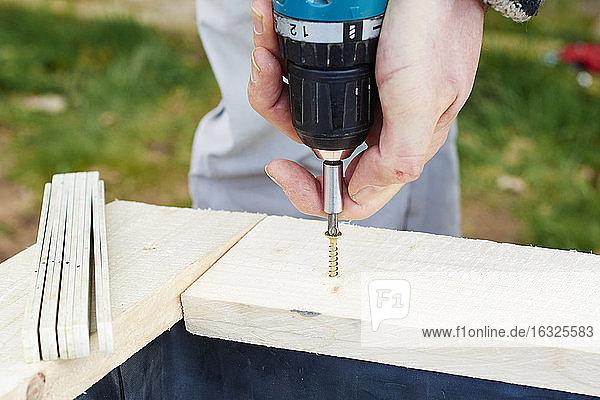 Gärtner schraubt Holzbohlen an  um ein Hochbeet zu bauen Gärtner schraubt Holzbohlen an, um ein Hochbeet zu bauen